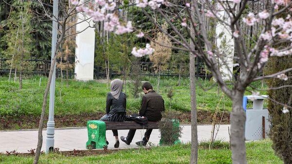 Молодые люди сидят на лавочке в парке Рудаки в Душанбе - Sputnik Тоҷикистон