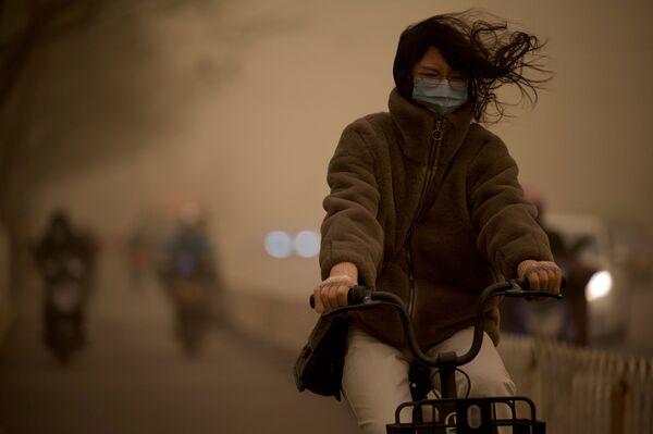 Девушка на велосипеде во время песчаной бури в Пекине  - Sputnik Таджикистан