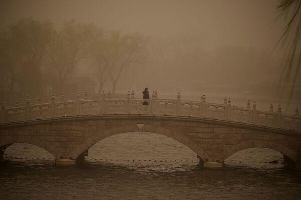 Девушка на мосту через озеро Хоухай во время песчаной бури в Пекине - Sputnik Таджикистан