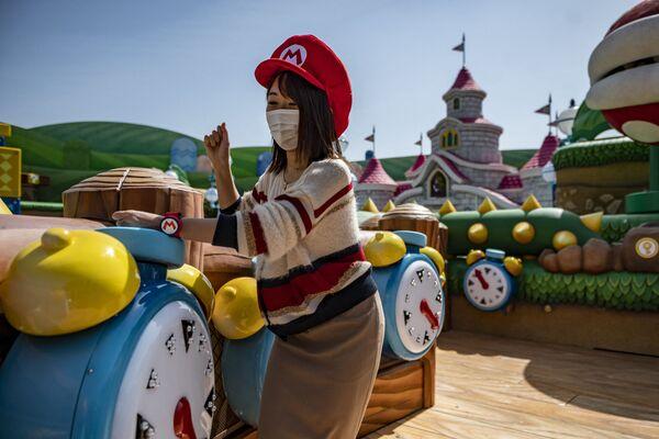 По всему парку играет музыка из популярной игры, а браслет, подключенный к смартфону, позволяет посетителям собирать виртуальные монеты, пробивая блоки, как итальянский сантехник - Sputnik Таджикистан