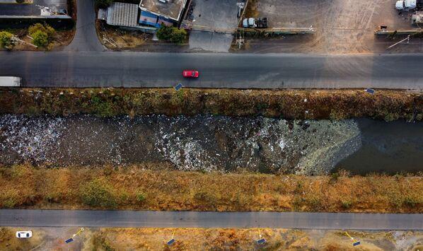 С воздуха видны автомобили, движущиеся рядом с каналом Interceptor Poniente, сильно загрязненным сточными водами и мусором, в Куаутитлане, штат Мехико, Мексика - Sputnik Таджикистан
