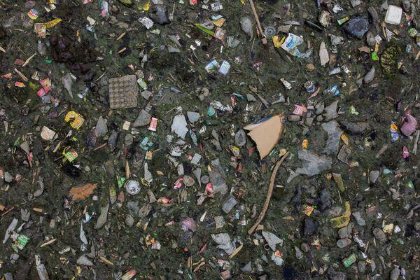 Бытовые отходы, плавающие в ручье реки Ситарум в Бандунге, Индонезия, 15 марта 2021 года. Правительство обязалось очистить реку Ситарум, которая считается одной из самых загрязненных в мире, и сделать ее воду пригодной для питья к 2025 году. Но бытовые и промышленные отходы продолжали течь в водоем - Sputnik Таджикистан