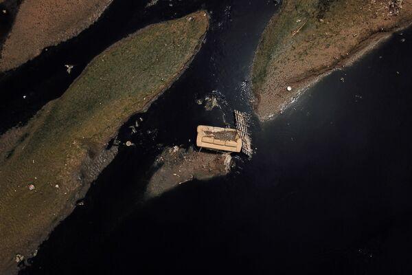 Выброшенный диван на реке Рио-Тиете рядом с экологическим парком Тиете в Сан-Паулу, Бразилия, 17 марта 2021 года. Река является одной из самых загрязненных в мире, хотя протекает через самые богатые города страны - Sputnik Таджикистан