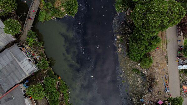 Люди ловят рыбу с деревянного моста на реке Писанг-Бату, протекающей через густонаселенный район и загрязненной бытовыми отходами, в Бекаси, на окраине Джакарты, Индонезия - Sputnik Таджикистан