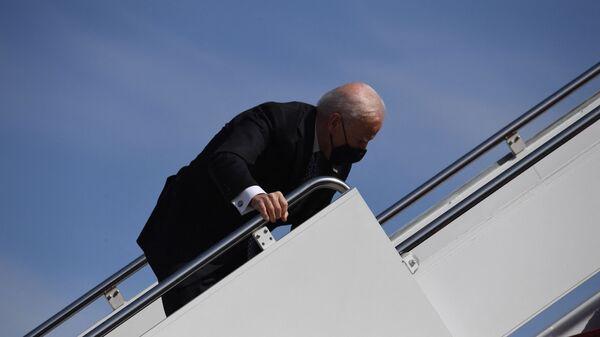 Президент США Джо Байден падает, восходя по трапу на самолет - Sputnik Тоҷикистон