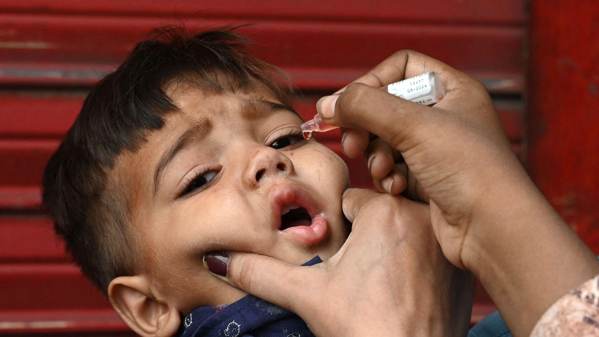 Медицинский работник вводит капли вакцины против полиомиелита ребенку - Sputnik Таджикистан, 1920, 17.09.2021