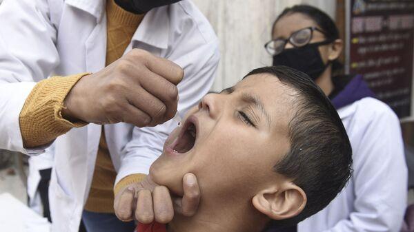 Медицинский работник вводит капли вакцины против полиомиелита ребенку - Sputnik Таджикистан