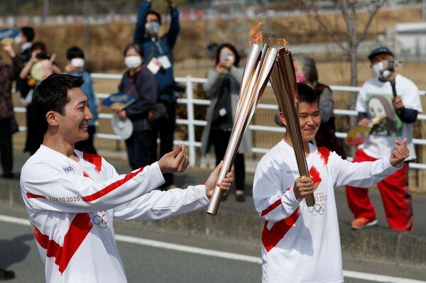 Факелоносцы с олимпийским огнем во время эстафеты в префектуре Фукусима  - Sputnik Таджикистан