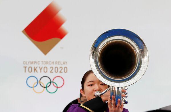 Участница оркестра  играет на музыкальном инструменте во время эстафеты Олимпийского огня в Токио - 2020 в префектуре Фукусима, Япония - Sputnik Таджикистан