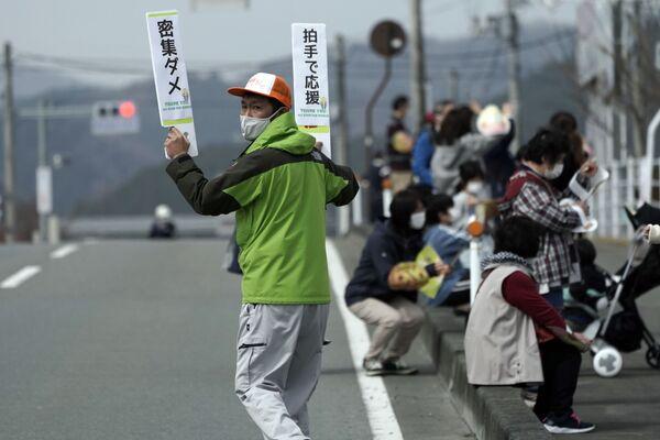 Мужчина с табличками во время эстафеты Олимпийского огня в Токио - 2020 в префектуре Фукусима, Япония - Sputnik Таджикистан