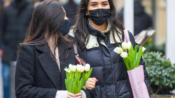 Девушки с букетами тюльпанов на улице  - Sputnik Таджикистан