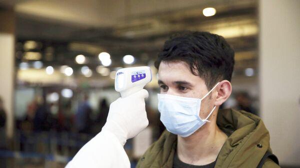 Афганский медработник проверяет температуру пассажира в качестве профилактической - Sputnik Тоҷикистон