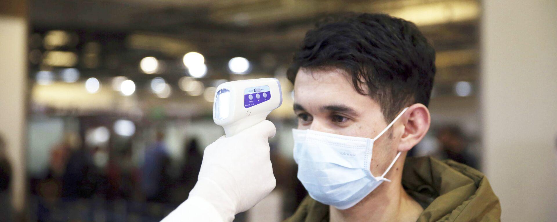 Афганский медработник проверяет температуру пассажира в качестве профилактической - Sputnik Таджикистан, 1920, 30.03.2021