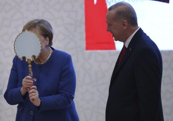 Канцлер Германии Ангела Меркель получает зеркало, подаренное президентом Турции Реджепом Тайипом Эрдоганом во время церемонии открытия нового кампуса турецко-германского университета в Стамбуле. 24 января 2020 года. - Sputnik Таджикистан