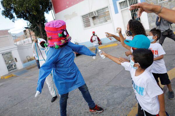 Дети прыскают алкоголем и антисептиком на человека в костюме коронавируса в Венесуэле - Sputnik Таджикистан