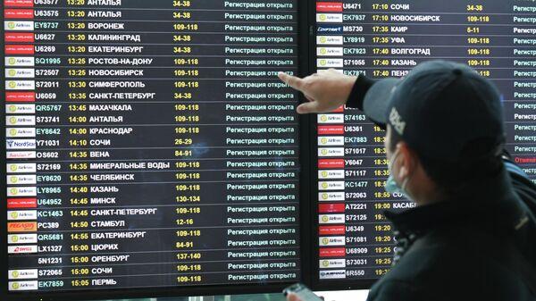 Мужчина возле электронного табло вылетов в аэропорту, архивное фото - Sputnik Таджикистан