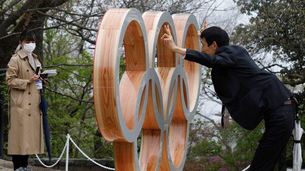 Мужчина фотографируется у Олимпийских колец после мероприятия по случаю 100 дней до Олийписких игр в Токио  - Sputnik Тоҷикистон