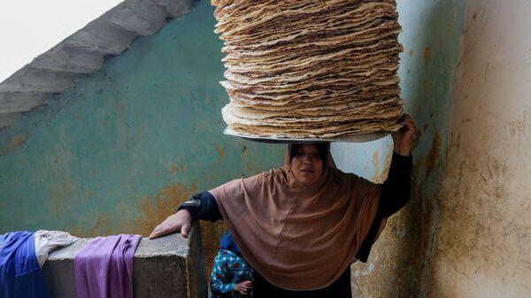 Верующая с хлебом на голове во время Рамадана в Египте  - Sputnik Таджикистан