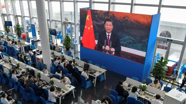 Журналисты смотрят экран, на котором президент Китая Си Цзиньпин выступает с речью на открытии Ежегодной конференции Боаоского азиатского форума (BFA) 2021 - Sputnik Таджикистан
