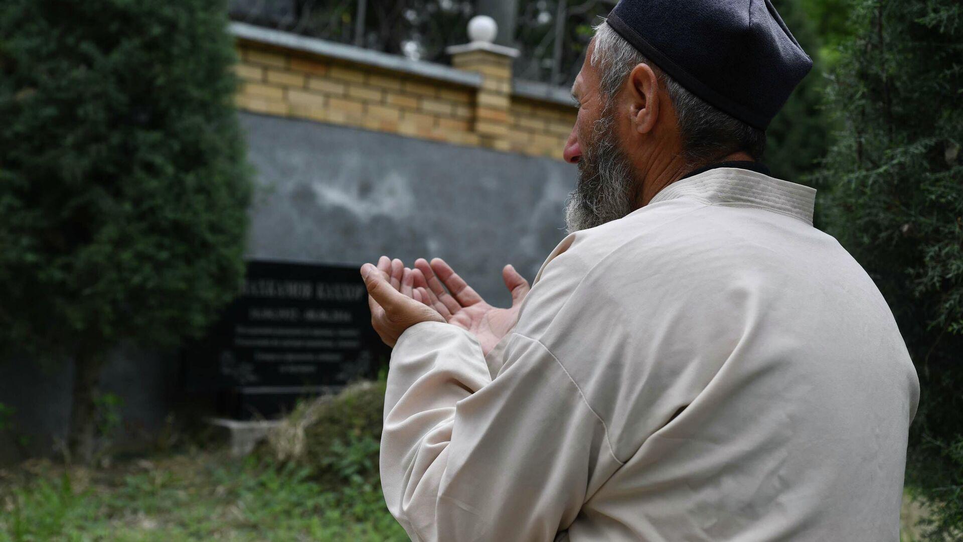 Мужчина молится на кладбище - Sputnik Таджикистан, 1920, 19.06.2021