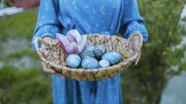 Корзина с крашеными голубыми яйцами на Пасху - Sputnik Таджикистан