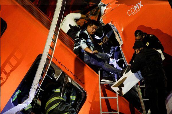 """Спасатели работают на месте частичного обрушения эстакады метро с вагонами на станции """"Оливос"""" в Мехико, Мексика, 3 мая 2021 года. Снимок сделан 3 мая 2021 года - Sputnik Таджикистан"""