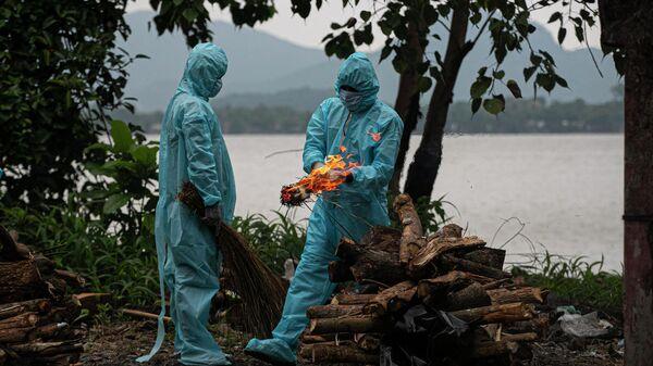 Мужчина в средствах индивидуальной защиты выполняет ритуалы кремации жертвы COVID-19 в Индии - Sputnik Тоҷикистон