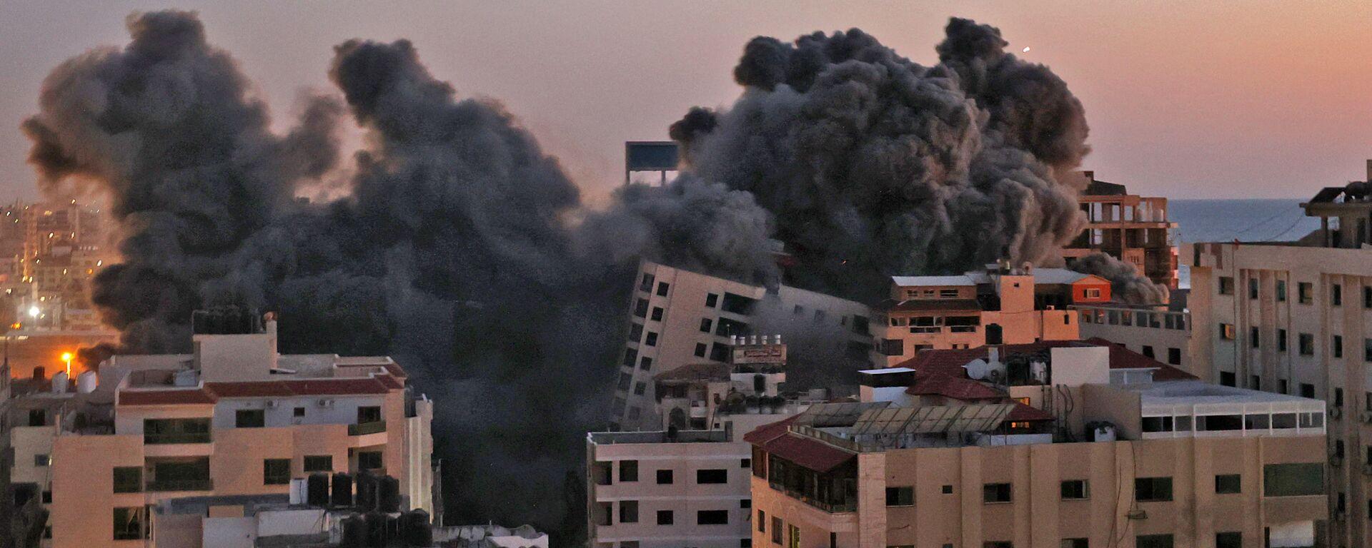 Пожарные тушат горящие многоквартирные дома после израильских авиаударов в городе Газа - Sputnik Тоҷикистон, 1920, 31.07.2021