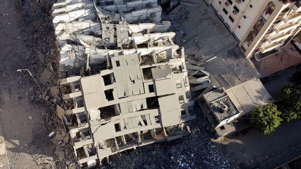 На снимке, сделанном с помощью беспилотника, видны руины здания, разрушенного в результате израильских воздушных ударов, на фоне вспышки израильско-палестинского конфликта в городе Газа - Sputnik Тоҷикистон