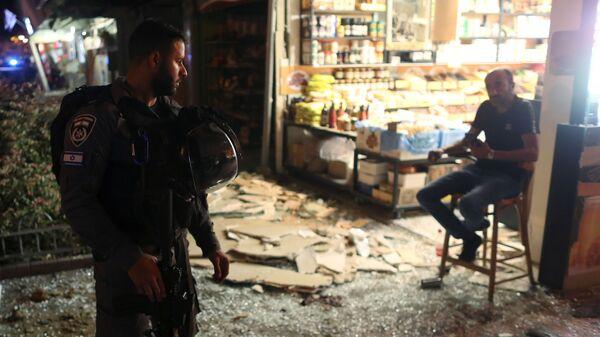 Сотрудник сил безопасности разговаривает с мужчиной на месте попадания ракеты, выпущенной из сектора Газа, в Холоне, Израиль - Sputnik Тоҷикистон