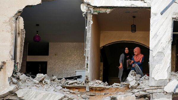 Палестинцы осматривают свой дома, который был поврежден в результате израильского авиаудара, на фоне вспышки израильско-палестинского конфликта, в городе Газа - Sputnik Таджикистан