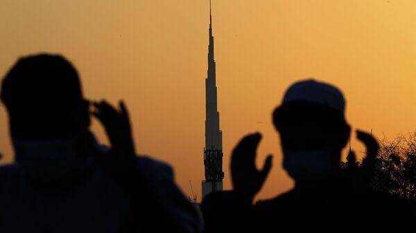 На фоне самого высокого здания в мире, Бурдж-Халифа, мусульманские мужчины в масках молятся, Дубай - Sputnik Тоҷикистон