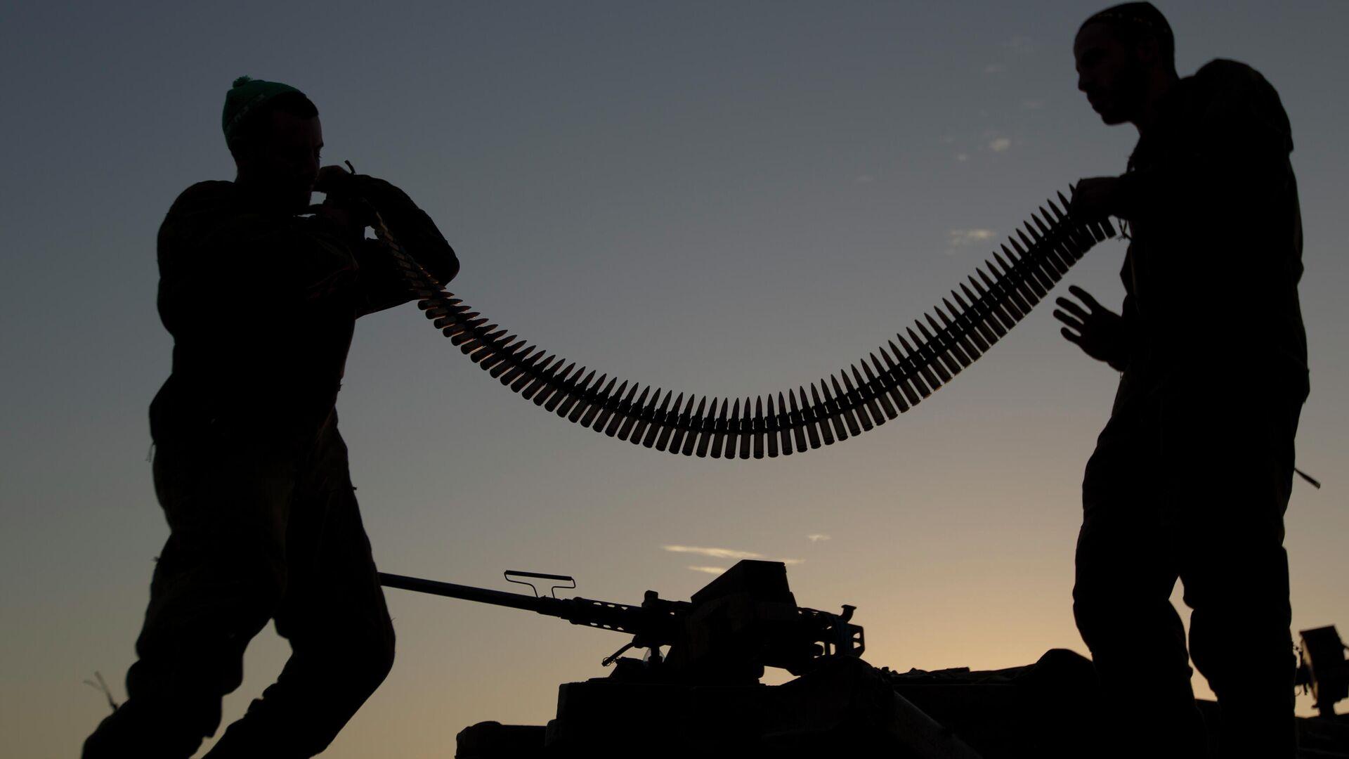 Израильские солдаты держат боеприпасы, стоя на крыше танка в плацдарме недалеко от границы с Израилем в Газе - Sputnik Тоҷикистон, 1920, 12.10.2021