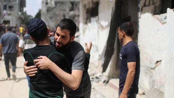 Палестинцы обнимаются друг с другом после возвращения в свои разрушенные дома после перемирия между Израилем и ХАМАС в Бейт-Хануне  - Sputnik Тоҷикистон