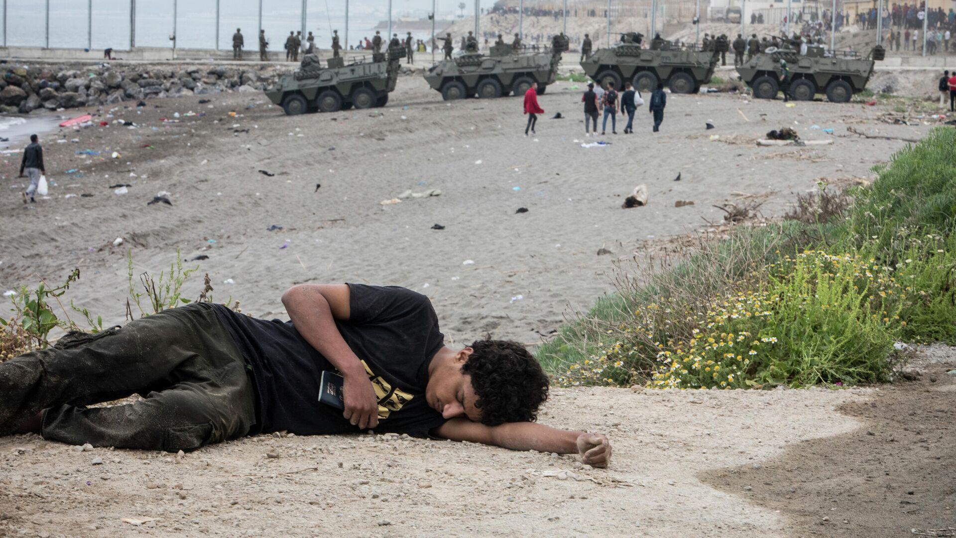 Мужчина лежит на земле после прибытия на испанскую территорию на границе Марокко и Испании - Sputnik Таджикистан, 1920, 25.05.2021