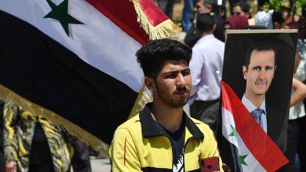 Участник митинга в поддержку президента Сирии Башара Асада в Дараа - Sputnik Таджикистан
