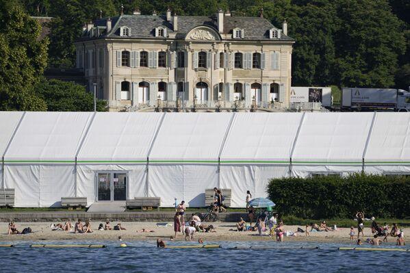 Посетители пляжа на Женевском озере рядом с пресс-центром, построенным на вилле Ла Гранж перед приездом Путина и Байдена. - Sputnik Таджикистан