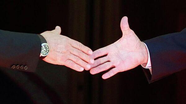 Президент Джо Байден и президент России Владимир Путин обмениваются рукопожатием  - Sputnik Тоҷикистон