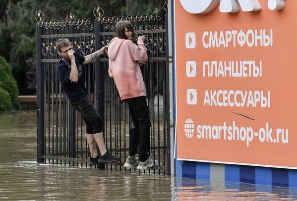 Люди ищут пути обхода на затопленных улицах, периодически перебираясь на заборы. - Sputnik Таджикистан
