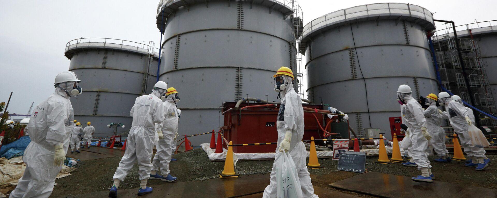 Сотрудники АЭС Фокусима в защитных костюмах и масках проходят мимо резервуаров для хранения радиоактивной воды в зоне H4 на атомной электростанции Фукусима - Sputnik Таджикистан, 1920, 25.06.2021