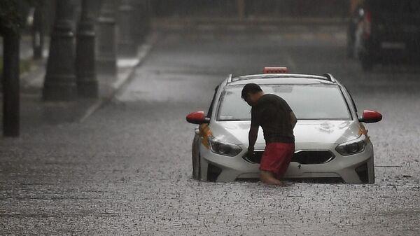 Водитель такси возле машины на затопленной улице в Москве - Sputnik Тоҷикистон