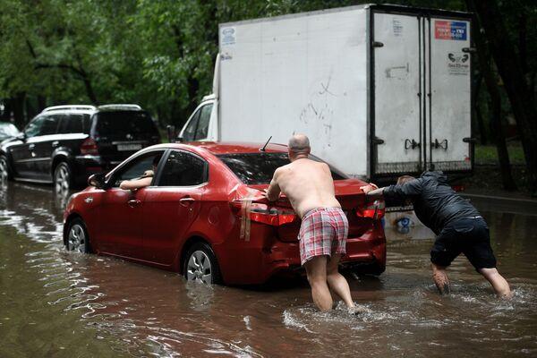 """Буквально через несколько минут городской транспорт """"поплыл"""" по дорогам. Люди выходили из автомобилей, чтобы хоть как-то вызволить машины из водного плена. - Sputnik Таджикистан"""