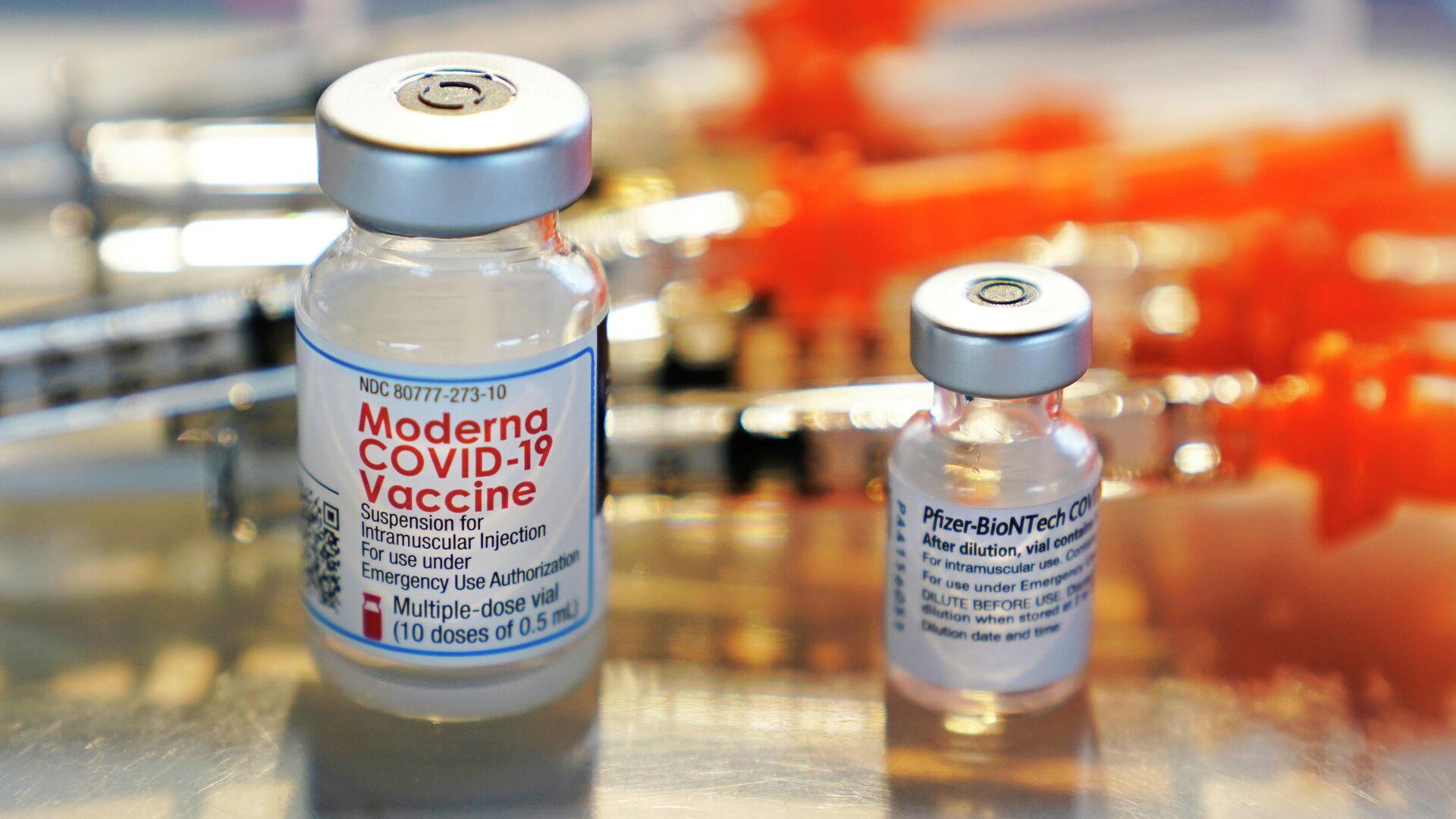 Флаконы с вакцинами Moderna и Pfizer COVID-19 выставлены на подносе в клинике - Sputnik Таджикистан, 1920, 26.07.2021