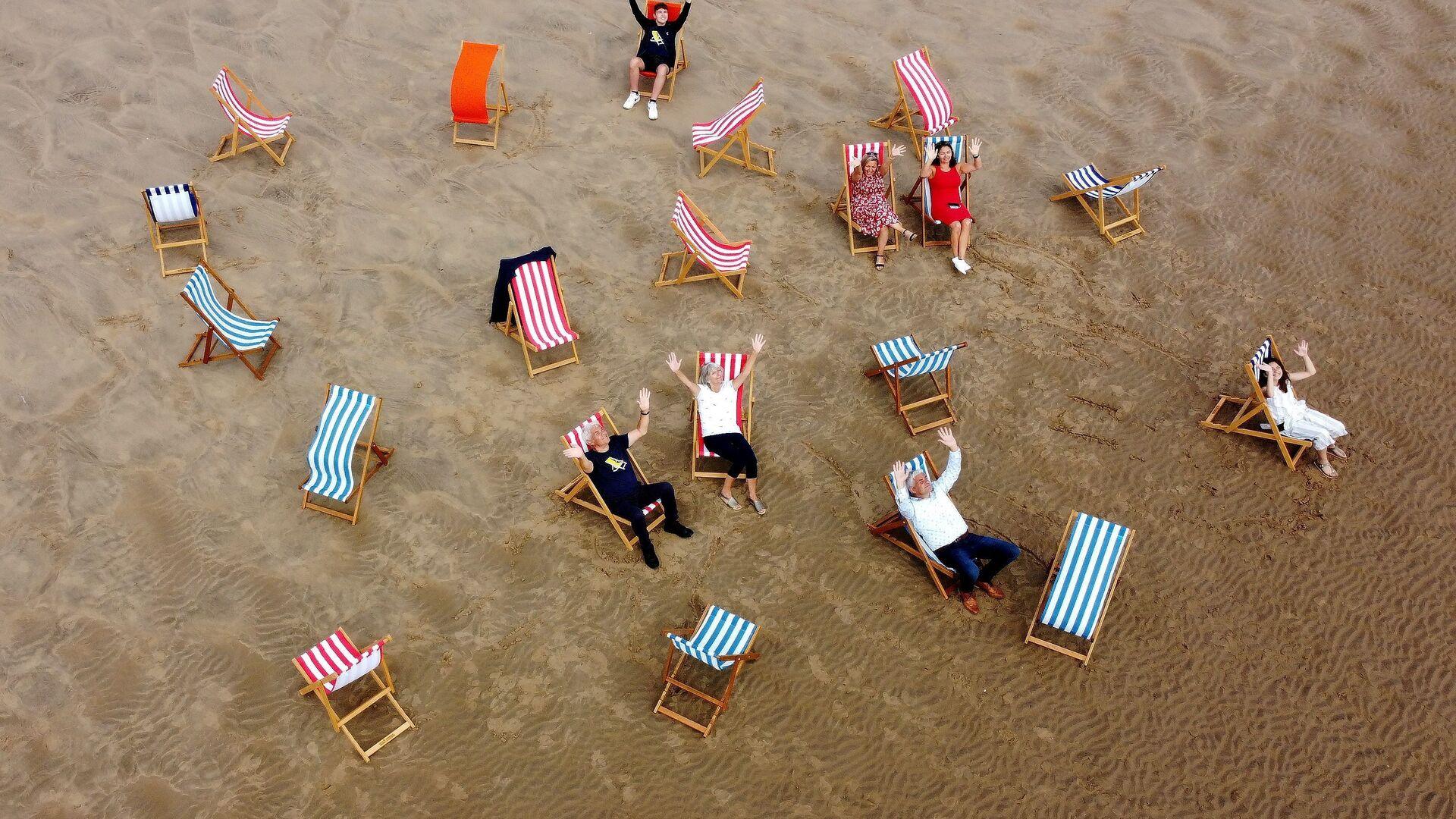 Люди позируют для фотографии, сидя в шезлонгах на пляже в Блэкпуле, Великобритания - Sputnik Тоҷикистон, 1920, 25.07.2021
