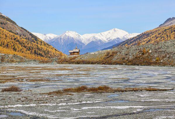 """Часовня у подножия Белухи на Алтае. Возведена в память о тех, кто не вернулся с гор - альпинистах, туристах, спасателях. В 2020-м церковь сгорела, но энтузиасты планируют ее восстановить.Гора Белуха - самая высокая на Горном Алтае. Местные считают, что именно там обитает """"хозяин края"""". - Sputnik Таджикистан"""