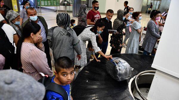 Пассажиры забирают багаж с транспортировочной ленты в аэропорту  - Sputnik Таджикистан