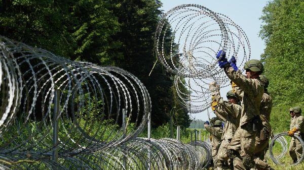 Солдаты литовской армии устанавливают забор из колючей проволоки на границе с Белоруссией в городе Друскининкай - Sputnik Тоҷикистон