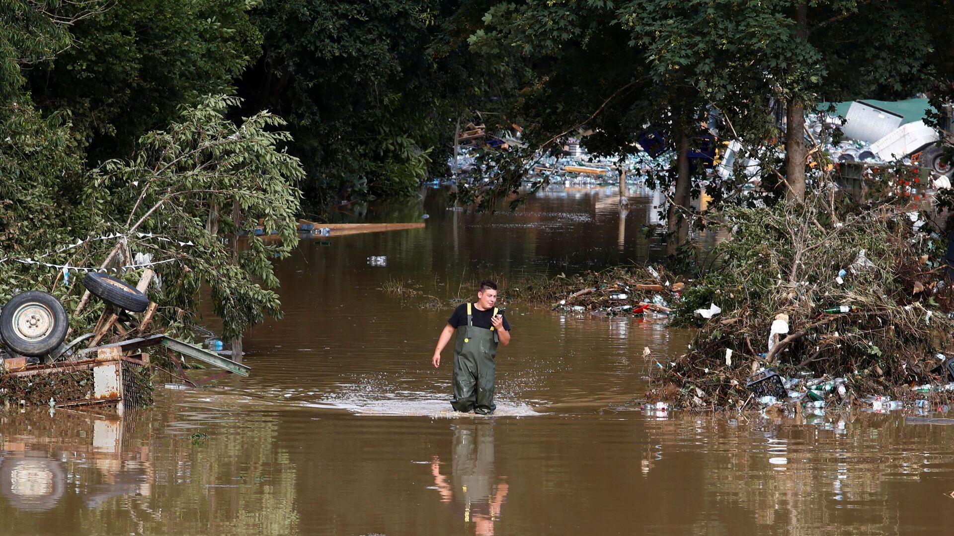 Мужчина идет по затопленному району, пострадавшему от наводнения после проливных дождей, в Бад-Нойенар-Арвайлере, Германия - Sputnik Тоҷикистон, 1920, 23.07.2021