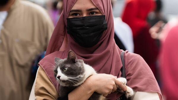 Мусульманка с котом после утренней молитвы в честь Курбан-байрама у Голубой мечети в городе Тагиг, Филиппины - Sputnik Таджикистан