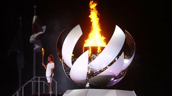 Наоми Осака из Японии держит олимпийский факел после зажжения олимпийского котла на церемонии открытия  - Sputnik Тоҷикистон